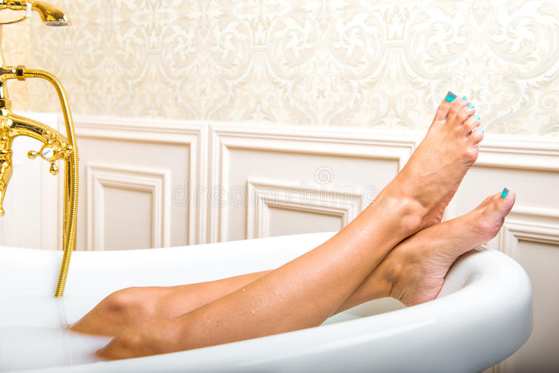 Πόδια γυναικών που βρίσκονται στην άσπρη μπανιέρα στοκ εικόνες