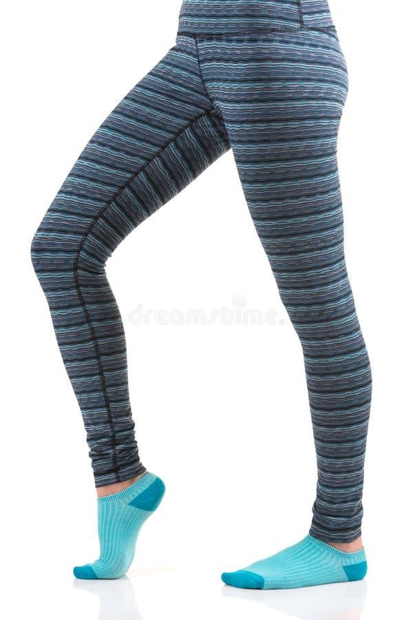 Πόδια γυναικών στα θερμικά εσώρουχα και μπλε κάλτσες από την πλάγια όψη που στέκεται σε ένα πόδι με άλλη κλίση στο πόδι γονάτων στοκ εικόνα