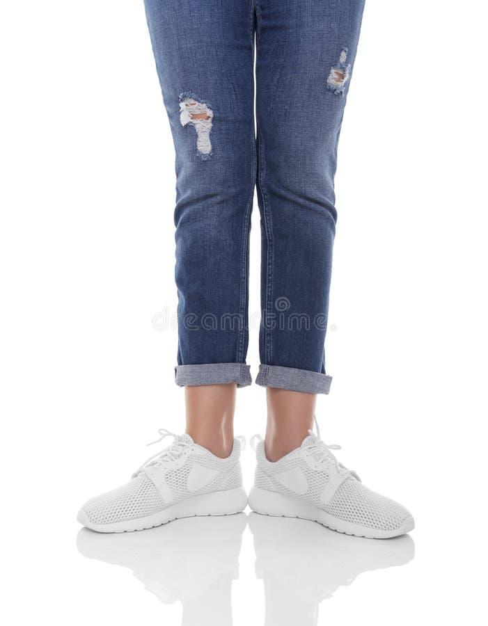 Πόδια γυναικών ` s στα τζιν και τα πάνινα παπούτσια στοκ φωτογραφίες με δικαίωμα ελεύθερης χρήσης
