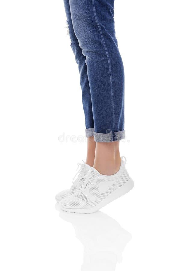Πόδια γυναικών ` s στα τζιν και τα πάνινα παπούτσια στοκ φωτογραφίες
