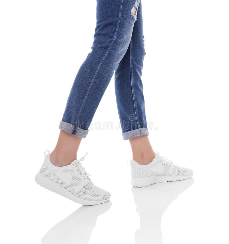 Πόδια γυναικών ` s στα τζιν και τα πάνινα παπούτσια στοκ εικόνα