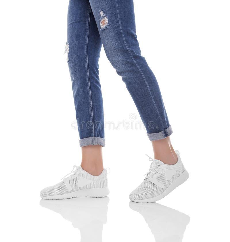Πόδια γυναικών ` s στα τζιν και τα πάνινα παπούτσια στοκ φωτογραφία με δικαίωμα ελεύθερης χρήσης