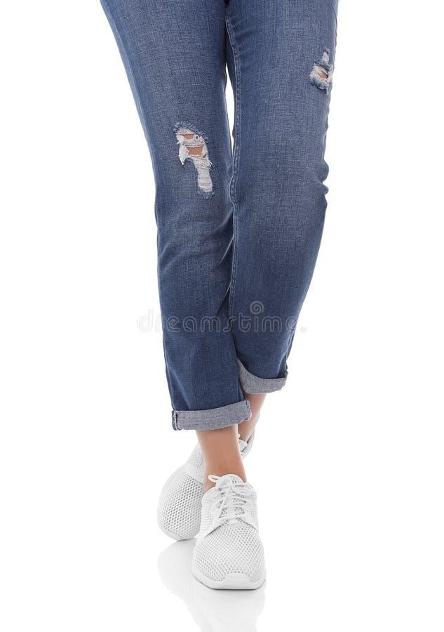 Πόδια γυναικών ` s στα τζιν και τα πάνινα παπούτσια στοκ εικόνες με δικαίωμα ελεύθερης χρήσης
