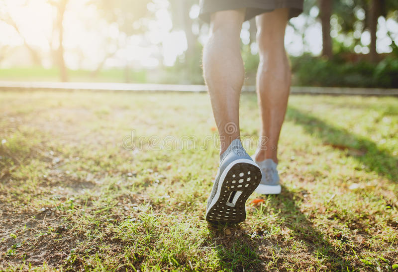 Πόδια ενός αθλητή που τρέχει σε μια κατάρτιση διαβάσεων πάρκων για την ικανότητα και τον υγιή τρόπο ζωής στοκ εικόνες