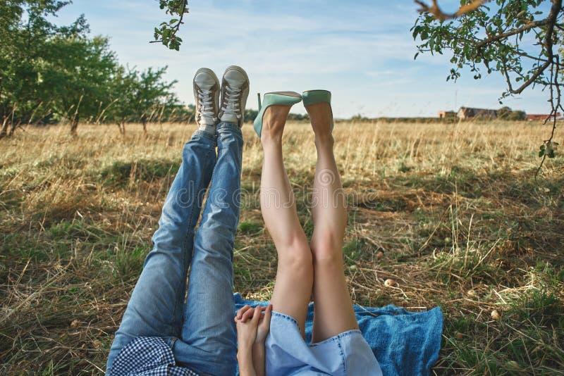 Πόδια ενός ζεύγους που βρίσκεται στη χλόη στον οπωρώνα μήλων στοκ εικόνες