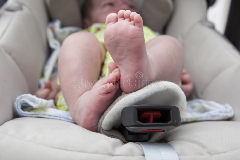 Πόδια ενός νεογέννητου αγοράκι στον περιπατητή στοκ φωτογραφίες
