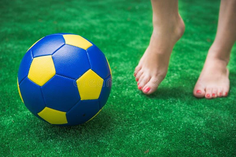 Πόδια και σφαίρα στην πράσινη χλόη στοκ εικόνες με δικαίωμα ελεύθερης χρήσης
