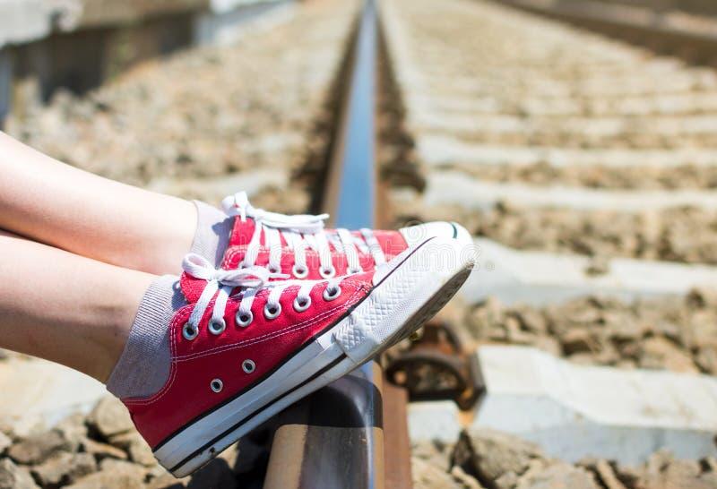 Πόδια κοριτσιών στα κόκκινα πάνινα παπούτσια που κάθονται από το σιδηρόδρομο στοκ εικόνες