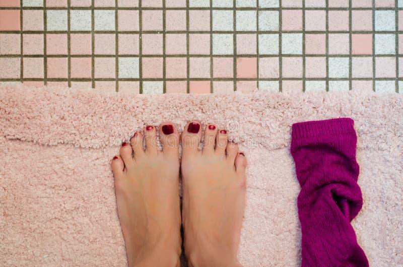 Πόδια μιας γυναίκας στο χαλί λουτρών στοκ φωτογραφία με δικαίωμα ελεύθερης χρήσης