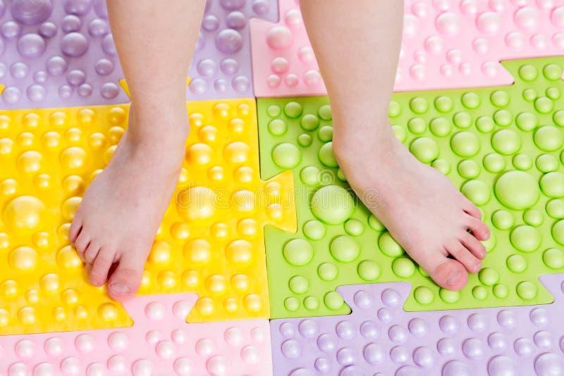 Πόδια παιδιών να τρίψει το χαλί στοκ φωτογραφία
