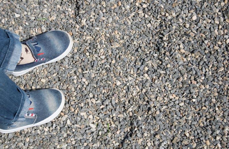 Πόδια παιδιών ` s σε ένα υπόβαθρο αμμοχάλικου στοκ φωτογραφία με δικαίωμα ελεύθερης χρήσης
