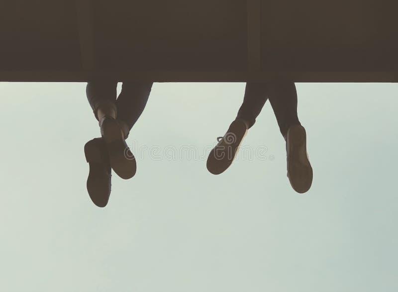Πόδια που κρεμούν από μια προεξοχή στοκ εικόνα με δικαίωμα ελεύθερης χρήσης