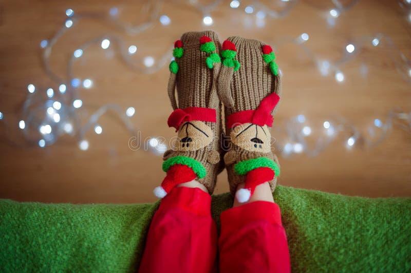 Πόδια στις κάλτσες κοντά στη γιρλάντα Χριστουγέννων στοκ εικόνες
