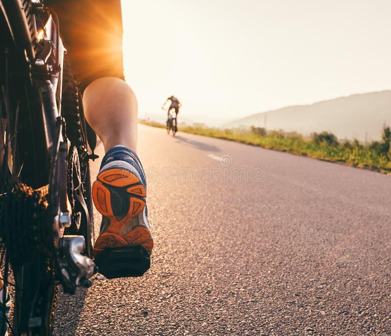 Πόδια στο πεντάλι bycikle στην ελαφριά στενή επάνω εικόνα ηλιοβασιλέματος στοκ φωτογραφία με δικαίωμα ελεύθερης χρήσης