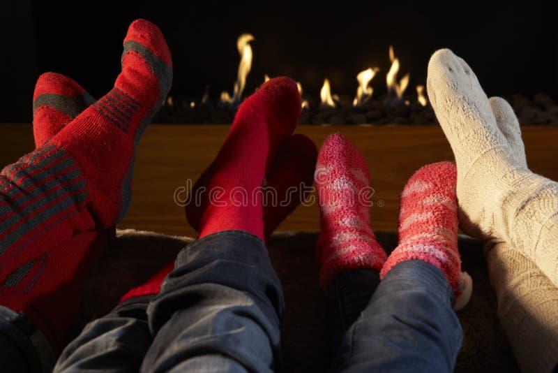 Πόδια τεσσάρων ζευγαριών στις κάλτσες που θερμαίνουν από την πυρκαγιά στοκ εικόνες