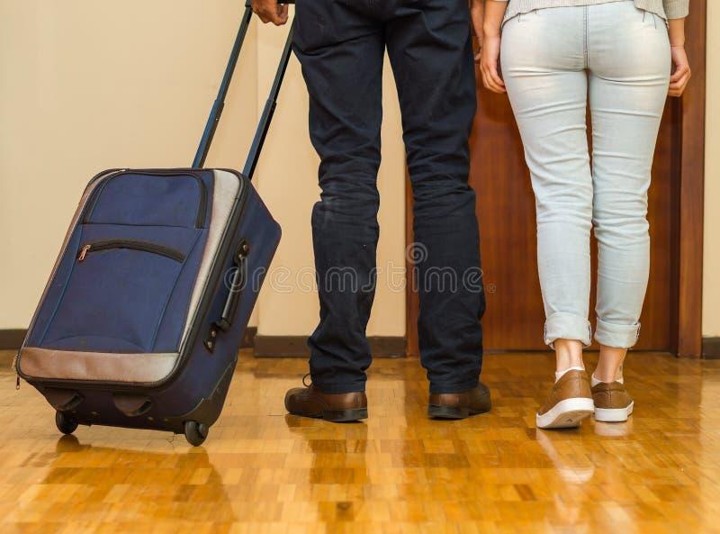 Πόδια του ζεύγους που φορούν τα περιστασιακά εσώρουχα που περπατούν προς την πόρτα που τραβά την μπλε βαλίτσα, έννοια φιλοξενουμέ στοκ εικόνα με δικαίωμα ελεύθερης χρήσης