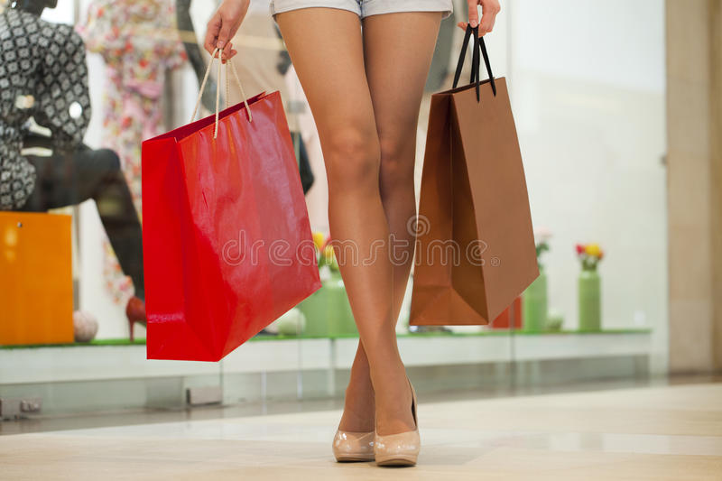 Πόδια των shopaholic φορώντας σορτς τζιν φέρνοντας διάφορο π στοκ εικόνες