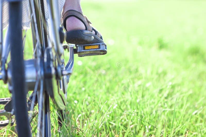 Πόδι γυναίκας στο πεντάλι ποδηλάτων στην πράσινη κινηματογράφηση σε πρώτο πλάνο χλόης στοκ φωτογραφία