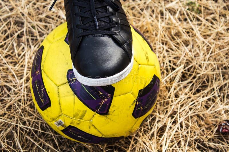 Πόδι της γυναίκας στα πάνινα παπούτσια και της σφαίρας ποδοσφαίρου σε έναν ξηρό τομέα στοκ εικόνα