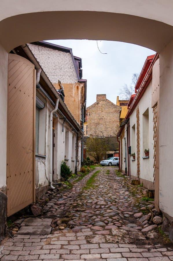 Πύλες αψίδων στη μεσαιωνική επίστρωσης οδό τελών πετρών βρώμικη αλλά μοντέρνη και άνετη με το σταθμευμένο αυτοκίνητο στην παλαιά  στοκ φωτογραφίες