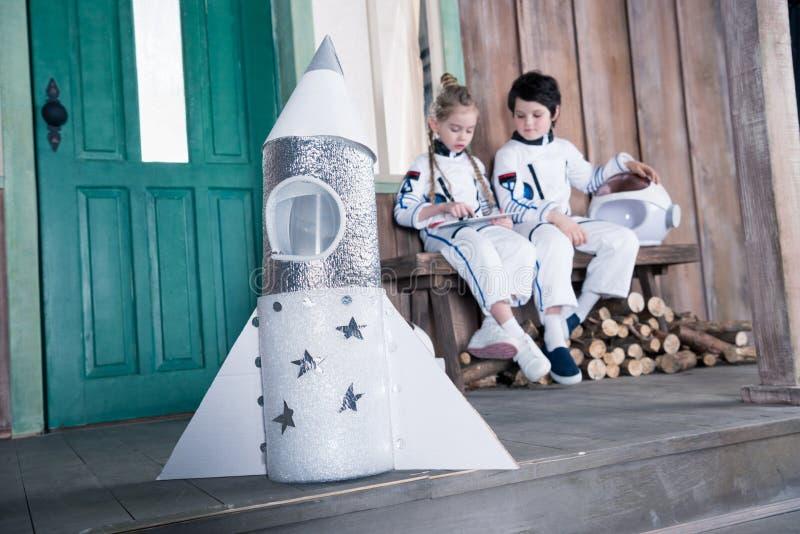 Πύραυλος παιχνιδιών και αστροναύτες παιδιών πίσω από τη χρησιμοποίηση της ταμπλέτας στοκ φωτογραφία με δικαίωμα ελεύθερης χρήσης