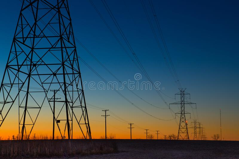 Πύργοι ηλεκτροφόρων καλωδίων κατά τη διάρκεια της μπλε ώρας στοκ εικόνες