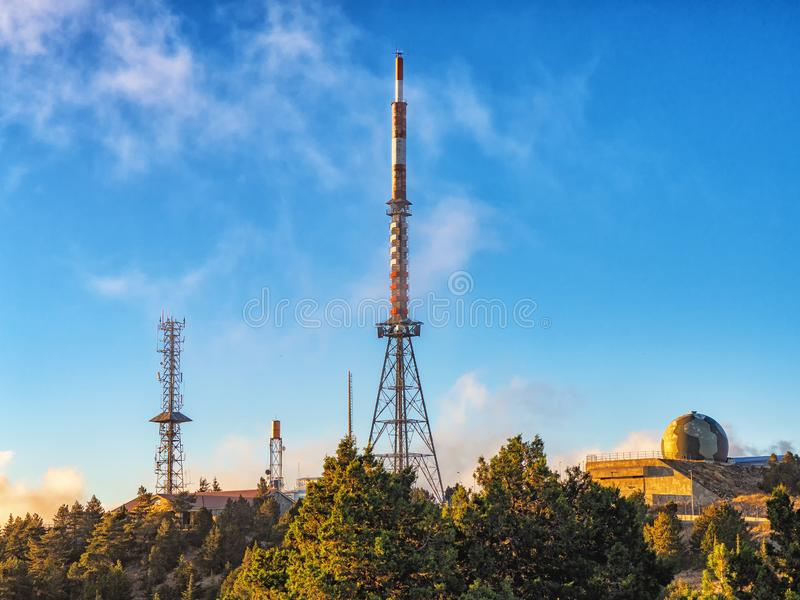 Πύργοι τηλεπικοινωνιών με τις κεραίες TV και δορυφορικό πιάτο στο ηλιοβασίλεμα στοκ εικόνες