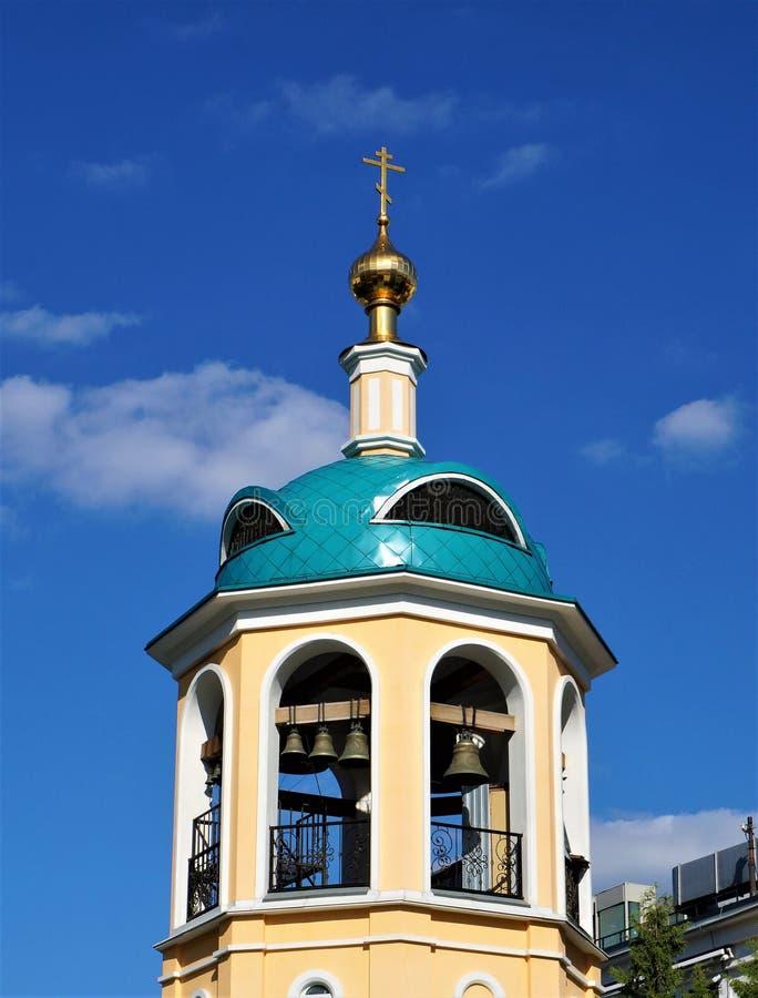 Πύργος κουδουνιών με έναν θόλο και ένας σταυρός ενάντια στο μπλε ουρανό στοκ εικόνα