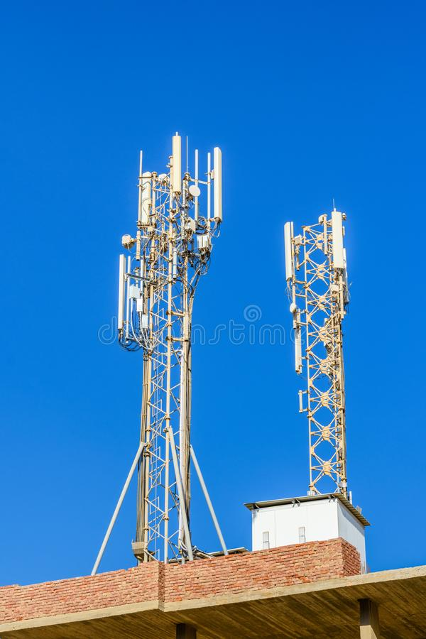 Πύργος τηλεπικοινωνιών με τις κεραίες ή ασύρματη συσκευή αποστολής σημάτων κεραιών επικοινωνίας ενάντια στο μπλε ουρανό στοκ εικόνες