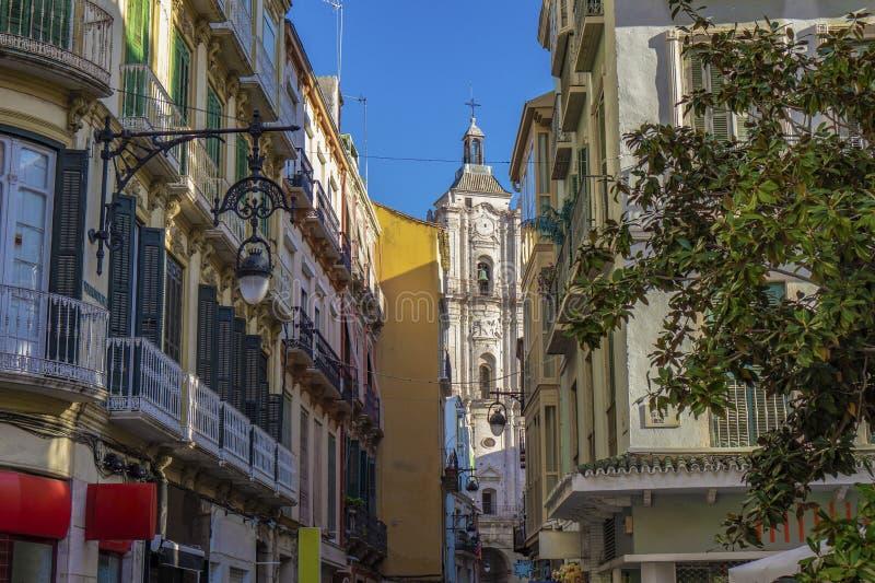 πύργος της εκκλησίας inglesia SAN Juan bautista στο τέλος μιας παλαιάς πόλης οδού narroe στη Μάλαγα Ισπανία στοκ φωτογραφία