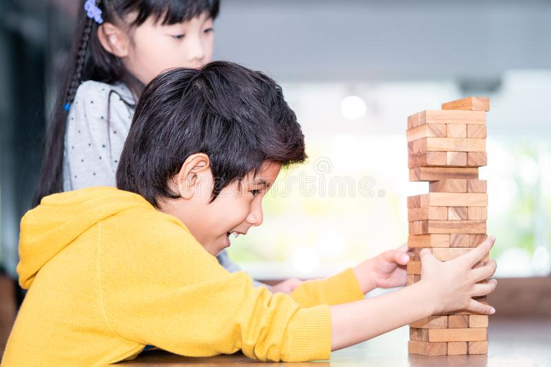 Πύργος φραγμών παιχνιδιών οικοδόμησης αγοριών με το φίλο στοκ εικόνες