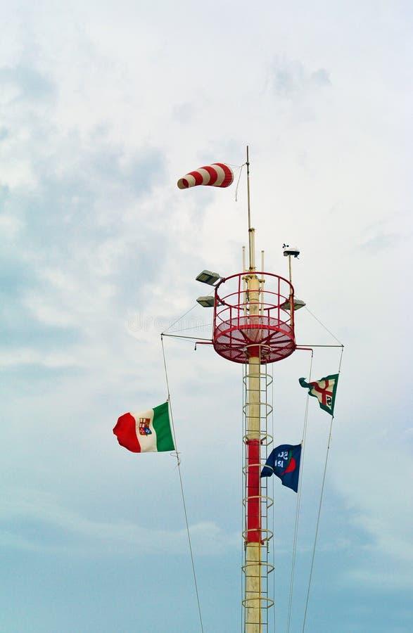 Πύργος Windsock στη θυελλώδη ημέρα Άσπρος και κόκκινος κωνικός σωλήνας, σημαίες χρώματος, νεφελώδης ουρανός στοκ εικόνα με δικαίωμα ελεύθερης χρήσης