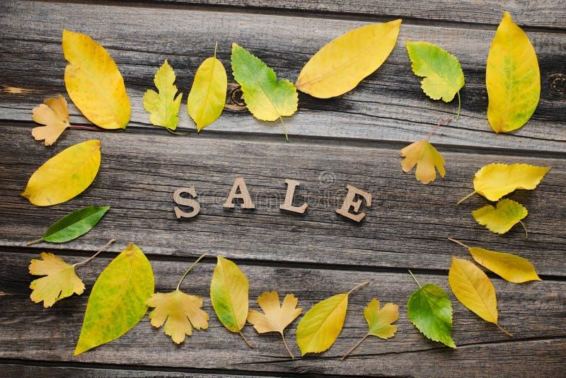 Πώληση επιγραφής σε ένα ξύλινο υπόβαθρο, πλαίσιο των κίτρινων φύλλων στοκ εικόνες