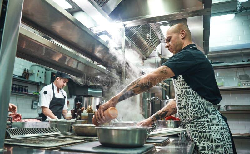 Πώς να μαγειρεψει έναν συγκεντρωμένο κρέας νέο αρχιμάγειρα στην ποδιά και τους μάγειρες που προετοιμάζουν τα τρόφιμα μαζί σε μια  στοκ εικόνες με δικαίωμα ελεύθερης χρήσης