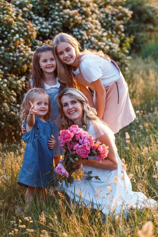 Π  οικογένεια μητέρας και τρεις χαριτωμένες κόρες με μικρά παιδιά Έννοια της ευτυχισμένης μητρότητας στοκ εικόνες