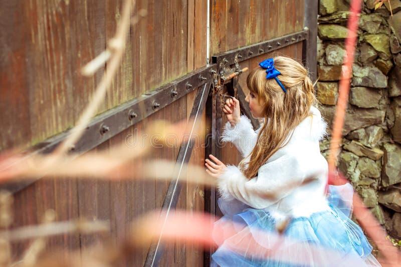 Πλάγια όψη ενός μικρού όμορφου κοριτσιού στο τοπίο της Alice στη χώρα των θαυμάτων που εξετάζει την κλειδαρότρυπα της πύλης στοκ εικόνες