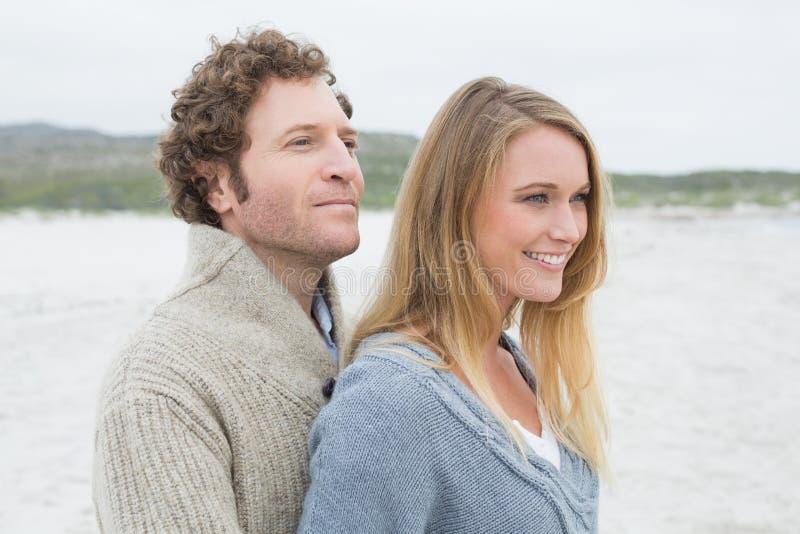 Πλάγια όψη ενός χαλαρωμένου νέου ζεύγους στην παραλία στοκ εικόνα
