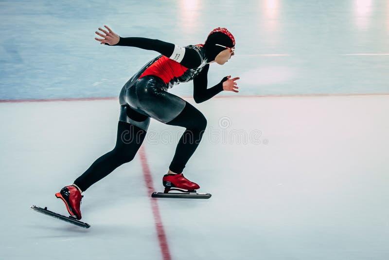 Πλάγια όψη κινηματογραφήσεων σε πρώτο πλάνο του θηλυκού σκέιτερ ταχύτητας διαδρομής αθλητών τρέχοντας στοκ εικόνα