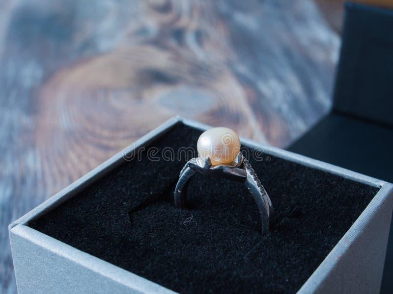 Πλάγια όψη σχετικά με το όμορφο δαχτυλίδι μαργαριταριών στο μαύρο κουτί στο ξύλινο υπόβαθρο στοκ εικόνα