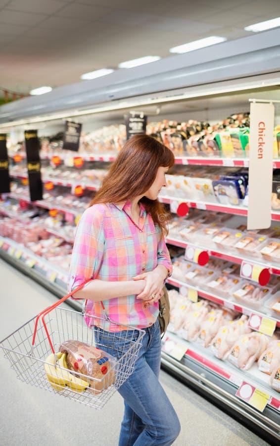Πλάγια όψη της γυναίκας που κάνει το παντοπωλείο που ψωνίζει με το καλάθι αγορών στοκ φωτογραφία με δικαίωμα ελεύθερης χρήσης