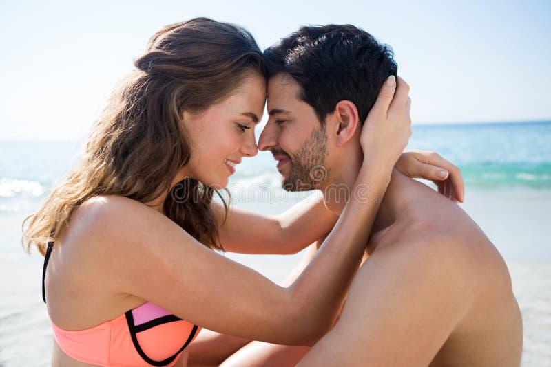 Πλάγια όψη της νέας συνεδρίασης ζευγών πρόσωπο με πρόσωπο στην παραλία στοκ φωτογραφία με δικαίωμα ελεύθερης χρήσης