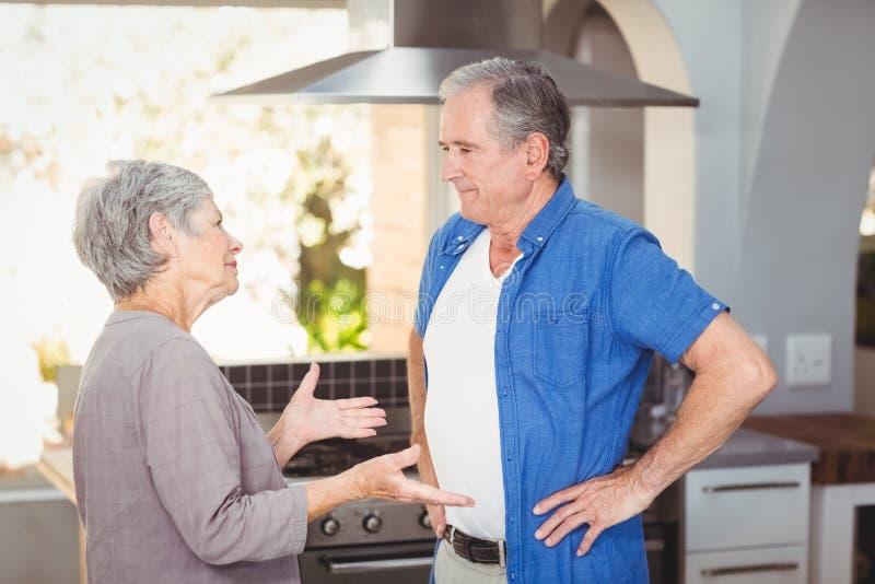 Πλάγια όψη του ανώτερου ζεύγους που υποστηρίζει στην κουζίνα στοκ εικόνες