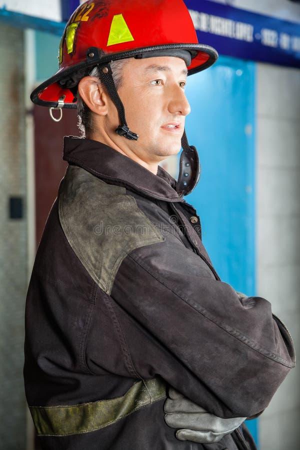 Πλάγια όψη του βέβαιου πυροσβέστη στο πυροσβεστικό σταθμό στοκ φωτογραφία με δικαίωμα ελεύθερης χρήσης
