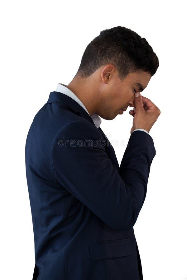 Πλάγια όψη του επιχειρηματία με επικεφαλής διαθέσιμο να πάσσει από τον πονοκέφαλο στοκ φωτογραφίες
