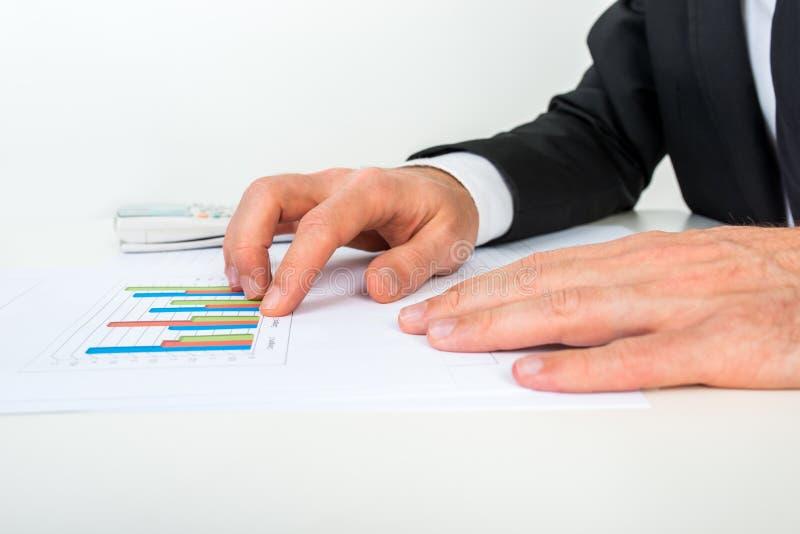 Πλάγια όψη του επιχειρηματία που αναλύει ένα σύνολο γραφικών παραστάσεων φραγμών στοκ εικόνα με δικαίωμα ελεύθερης χρήσης