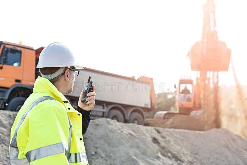 Πλάγια όψη του επόπτη που χρησιμοποιεί walkie-talkie στο εργοτάξιο οικοδομής ενάντια στο σαφή ουρανό στοκ εικόνες με δικαίωμα ελεύθερης χρήσης