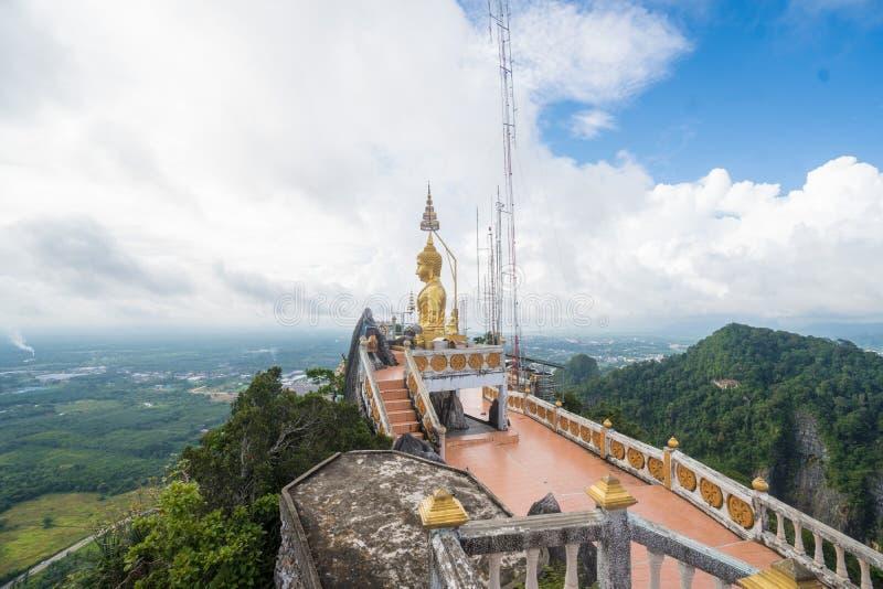 Πλάγια όψη του μεγάλου χρυσού αγάλματος του Βούδα ενάντια στο νεφελώδη ουρανό στο ναό σπηλιών τιγρών στοκ φωτογραφία με δικαίωμα ελεύθερης χρήσης