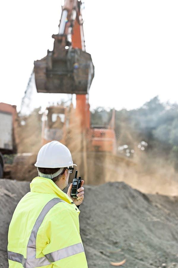 Πλάγια όψη του μηχανικού που χρησιμοποιεί walkie-talkie στο εργοτάξιο οικοδομής στοκ φωτογραφία με δικαίωμα ελεύθερης χρήσης