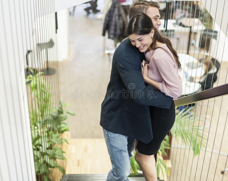 Πλάγια όψη του νέου επιχειρησιακού ζεύγους που αγκαλιάζει στη σκάλα στοκ εικόνες με δικαίωμα ελεύθερης χρήσης