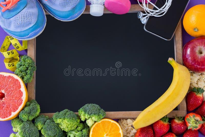 Πλάκα που περιβάλλεται με τα εξαρτήματα ικανότητας και τα διάφορα φρούτα και λαχανικά στοκ φωτογραφία